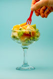 手为叉子在一块美丽的玻璃的切的果子到达在蓝色背景 免版税库存图片