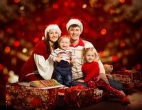 圣诞节家庭四人,母亲父亲孩子,红色 免版税库存照片