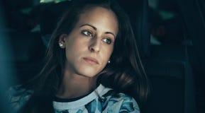 哀伤的少妇女孩哭泣的坐在汽车里面 免版税库存照片