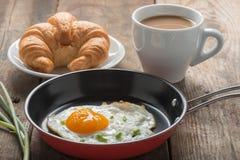 在平底锅的早餐煎蛋用咖啡,新月形面包 免版税图库摄影