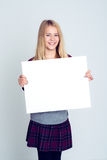 显示一个白色标志的好白肤金发的女孩 免版税库存照片