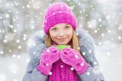 有杯子的微笑的少妇在冬天森林里 图库摄影