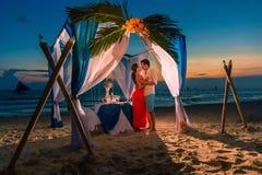 年轻美好的夫妇吃浪漫晚餐在日落 免版税库存图片