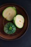 在赤土陶器盘的圆的绿色意大利夏南瓜 库存图片