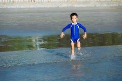 男孩跑到海 免版税库存照片