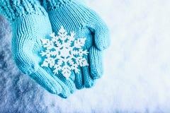 在轻的小野鸭的女性手编织了有闪耀的美妙的雪花的手套在白色雪背景 冬天圣诞节概念 免版税库存图片
