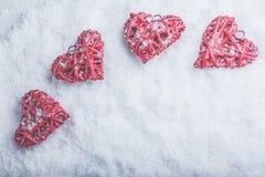 在白色冷淡的雪背景的四美好的浪漫葡萄酒心脏 爱和圣情人节概念 库存图片