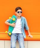 佩带一件方格的衬衣、太阳镜和滑板的时髦的少年男孩 免版税库存照片
