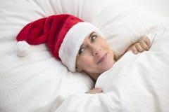 妇女在与圣诞老人帽子的床上 免版税库存照片