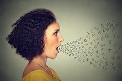 妇女谈话与字母表在从她的嘴出来上写字 通信情报概念 免版税库存图片