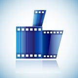 有拇指的卷曲的蓝色戏院磁带影片人的手 库存图片