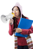 冬天穿戴的女小学生呼喊与扩音机的 免版税库存图片