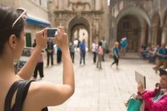 拍与她的智能手机的少妇一张照片 捕捉记忆的妇女游人 在城市附近的旅游游览 少妇游览 库存图片
