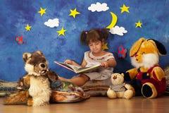 小女孩对她的读书故事充塞了玩具朋友 免版税库存图片