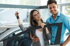 庆祝一辆汽车的购买的年轻夫妇在汽车陈列室里 图库摄影