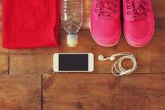 与手机的健身概念有毛巾的和妇女炫耀在木背景的鞋类 图库摄影