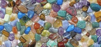 多彩多姿的翻滚的水晶向背景扔石头 免版税库存图片