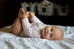 放松和使用与她的脚趾的女婴 免版税图库摄影