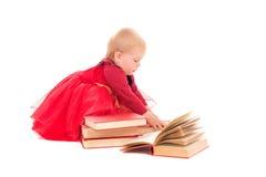 红色褂子阅读书的女婴 免版税图库摄影