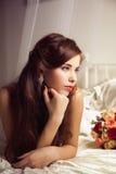 美丽的新娘的早晨在床上 免版税库存图片