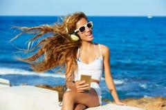 白肤金发的在海滩的孩子青少年的女孩耳机音乐 免版税库存照片