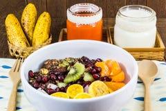 与坚果、混合果子,牛奶和红萝卜汁的巧克力格兰诺拉麦片 库存照片
