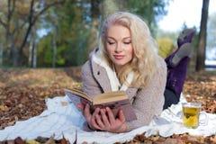 说谎在地面上的美丽的逗人喜爱的愉快的微笑的女孩和在秋天公园读一本书有一个杯子的公园热的茶 免版税库存图片