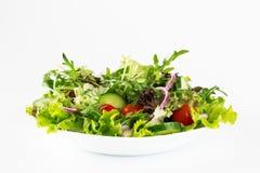 在白色隔绝的板材的新鲜的沙拉 免版税库存图片