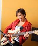 伸出舌头的快乐的吉他弹奏者,当时 免版税库存照片