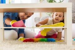 Οικογενειακό καθαρίζοντας σπίτι ομαδικής εργασίας με τις σφουγγαρίστρες Στοκ Φωτογραφίες