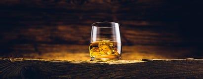 在老桌上的威士忌酒玻璃 图库摄影