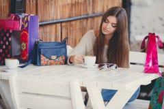 一个咖啡馆的迷人的妇女一杯咖啡的 图库摄影