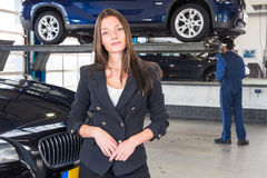 站立在她固定的汽车前面的喜悦的顾客 免版税库存照片