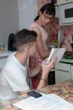 做家庭作业的母亲和儿子的画象 免版税库存图片