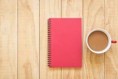 红色书和咖啡杯顶视图在木桌上 免版税图库摄影