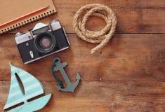 空白的笔记本、木风船、船舶绳索和照相机的顶视图图象 旅行和冒险概念 减速火箭的被过滤的图象 免版税库存照片