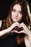 做心脏形状爱标志用手的青少年的女孩 库存图片