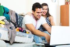 Молодые супруги просматривая сеть и пакуя багаж Стоковые Изображения RF