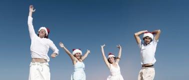 庆祝在圣诞节概念的海滩的两对夫妇 免版税库存图片