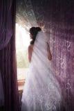 看通过窗口的一套白色婚礼礼服的美丽的新娘 免版税库存照片