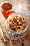 在玻璃瓶子和蜂蜜的自创健康格兰诺拉麦片 库存图片