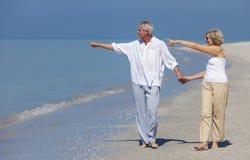 愉快的资深夫妇走的指向拿着手海滩 免版税库存图片