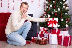 投入圣诞节礼物箱子的年轻人在圣诞树下 库存照片