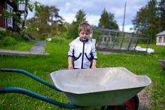 在独轮车附近的逗人喜爱的年轻男婴在庭院里 库存图片