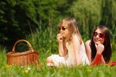 母亲和女儿有野餐在公园 免版税库存照片