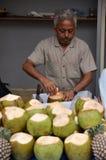 未知的印地安的销售在街道上的椰子 免版税库存图片