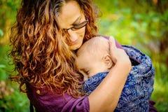 在公园照顾拿着一个男婴在她的手上 免版税图库摄影