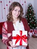 拿着圣诞节礼物箱子的年轻美丽的妇女画象  图库摄影