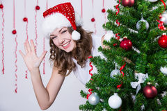 圣诞老人帽子的俏丽的妇女在圣诞树附近 库存图片