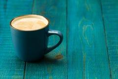 在蓝色木背景的咖啡杯 免版税库存照片